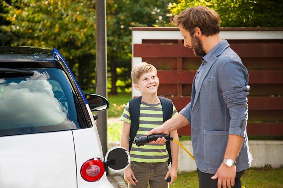 Papa und Sohn beim Betanken eines E-Fahrzeugs