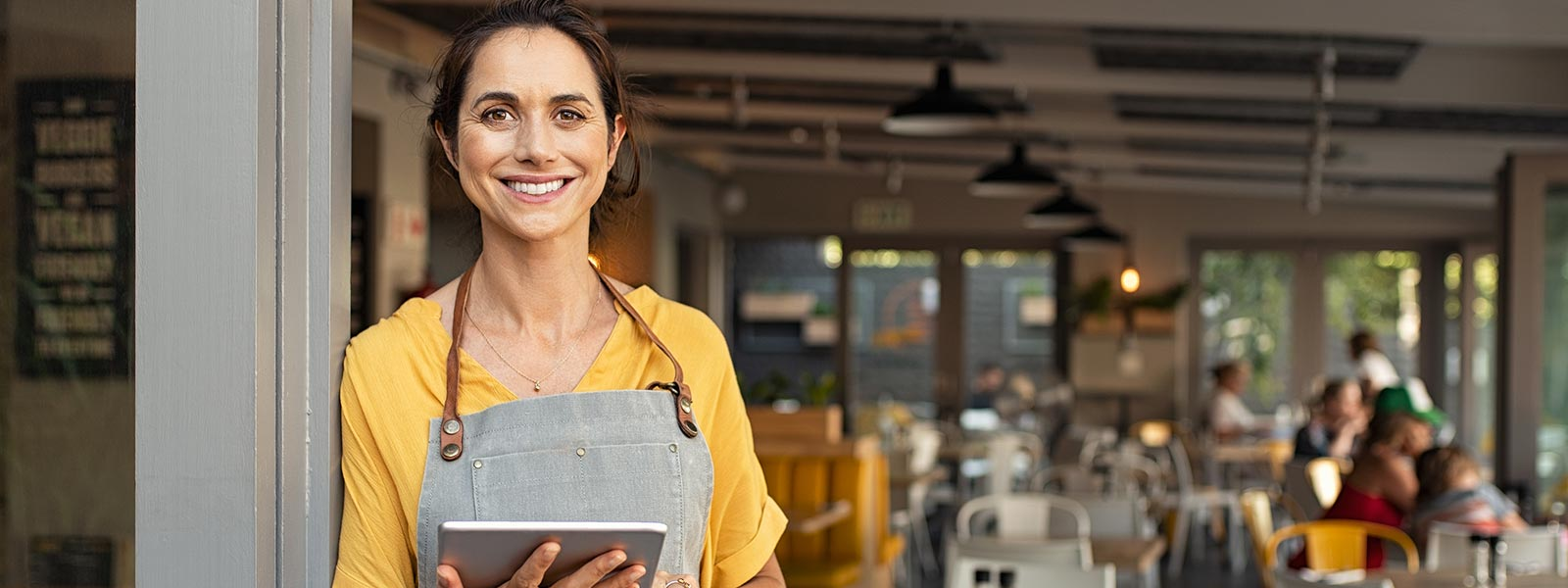 Bedienung in einem Café mit Tablet in der Hand, im Hintergrund Gäste