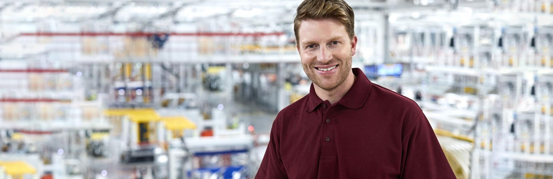 Lächelnder Mann in einer Industriehalle