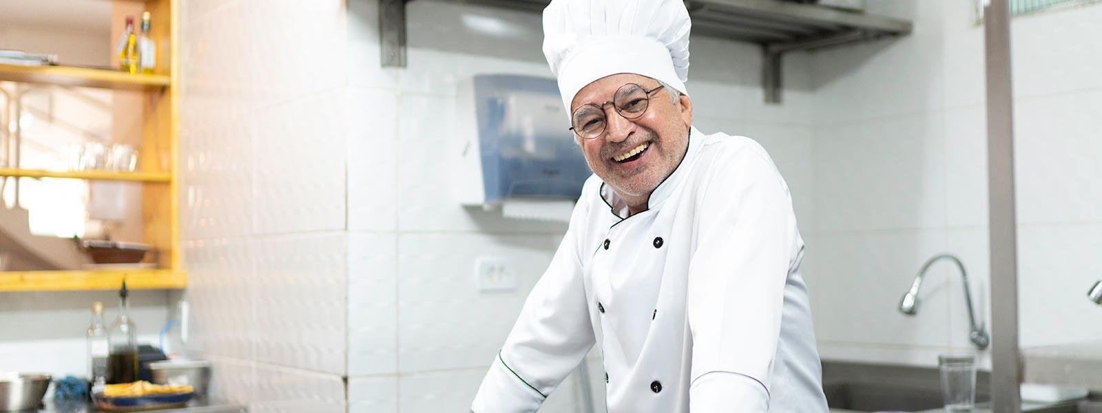 freundlicher Mann mit Kochmütze in einer Restaurant-Küche