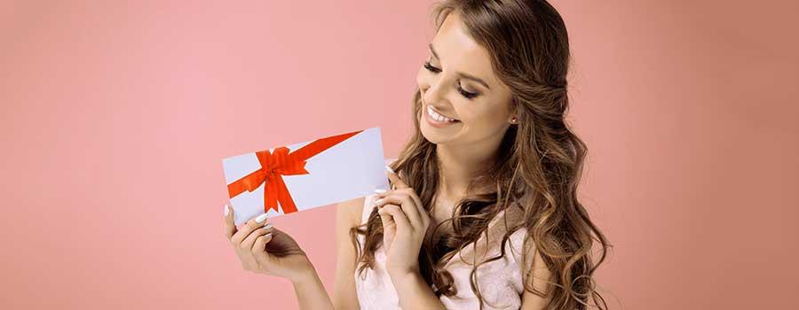 lächelnde Frau mit Geschenkgutschein in der Hand